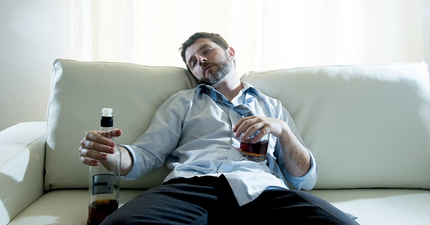 Businessman wearing blue shirt drunk at desk on white background