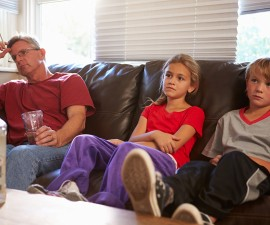 Father Sits On Sofa With Children Smoking And Drinking