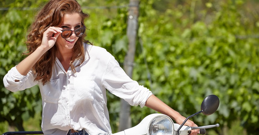 Young beautiful woman sitting on a italian scooter in tuscany ou